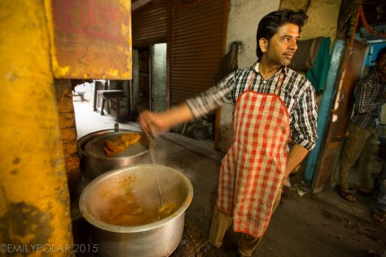 Indian man wearing apron cooking mutton in big pot outside of a restaurant in Old Delhi, India.