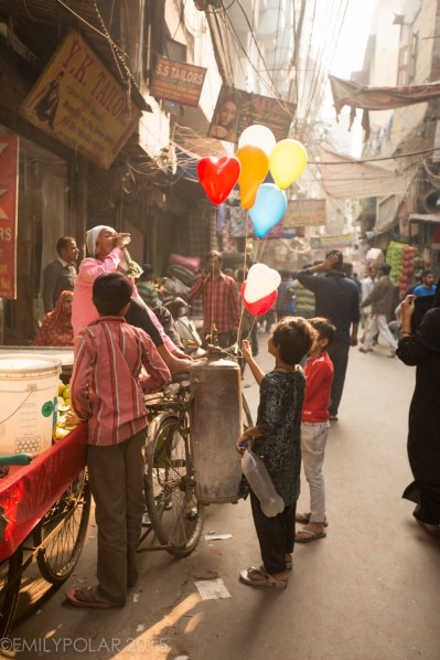 Kids buying colorful balloons at a small street stand in Old Delhi, India.