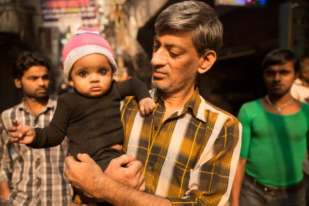 Indian baby girl wearing eyeliner and cute hat in the streets of Old Delhi.
