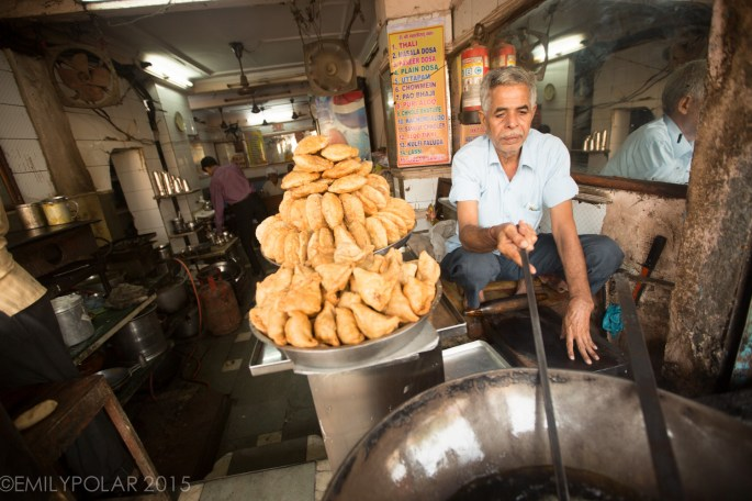 Indian man frying dough and somosa at restaurant in Old Delhi, India.