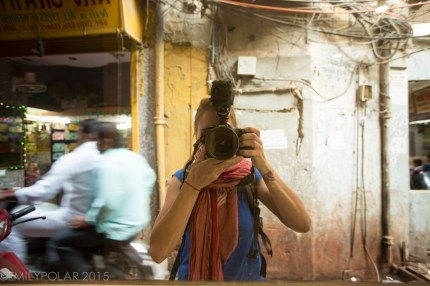 Emily Polar taking a selfie with Canon Mark lll and Rode Mic Pro in a window reflection in the streets of Old Delhi.