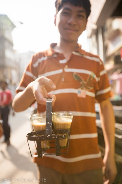 Indian boy standing with a to go tray of Chai ready for delivery in Old Delhi, India near Chawri Bazar.