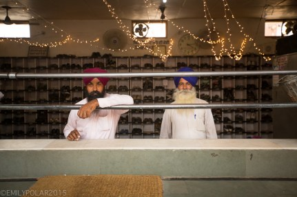 Two Sikh men with turbans and beards work the shoe check at the tower near the Golden Temple in Amritsar, Punjab.
