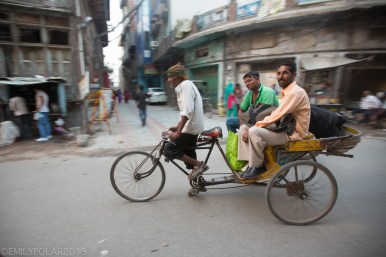Two Indian men being pulled by their rickshaw driver in the streets of Amritsar.