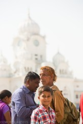 Young Indian boy looks at the camera while walking along the white marble near the clock tower at the Golden Temple.