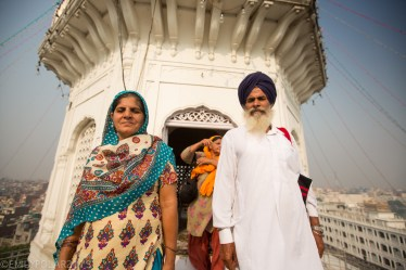 Portrait of a Punjabi man and woman smiling at the Golden Temple in Amritsar.