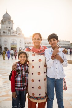 A cute mother with her two sons smiling for the camera at the Golden Temple.