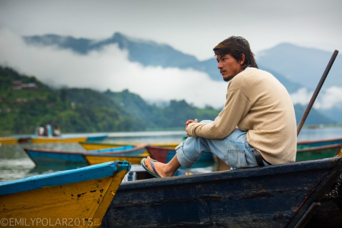 Nepali man sitting on a boat chilling on Pokhara lake on a cloudy day in Nepal.
