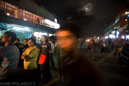 Nepali boys face blurs as he walks by my camera at night lit up by street lights in Pokhara, Nepal.