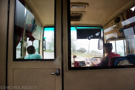 View of Nepali bus driver through the front bus door turning the big wheel steering us through the rain and mud.