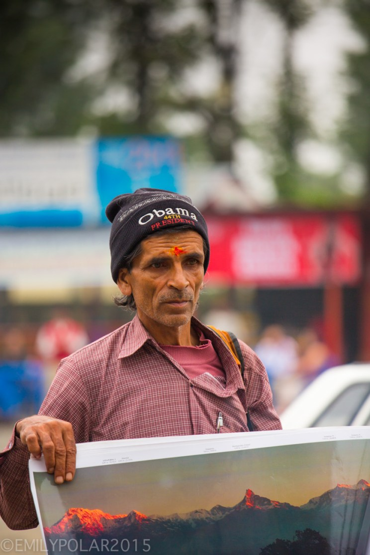 Nepali man wearing an Obama hat selling posters at the bus station in Pokhara, Nepal.