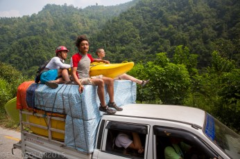 Kayakers riding on top of truck with kayaks stacked up in back driving to the river in Nepal.