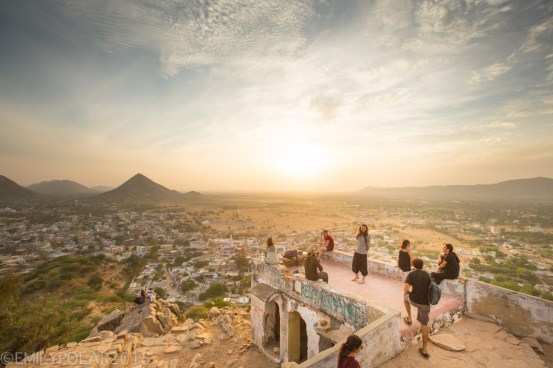 Group of travelers stand on part of Gayatri Temple overlooking Pushkar at sunrise.