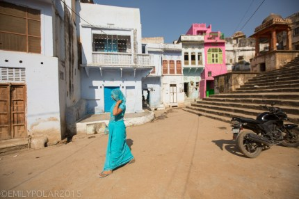 Indian woman wearing blue sari with head covered and flip flops walks along dirt street in Pushkar.