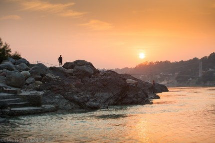 Man standing on the rocks along the Ganges at sunset near Ram Jhula Bridge in Rishikesh.