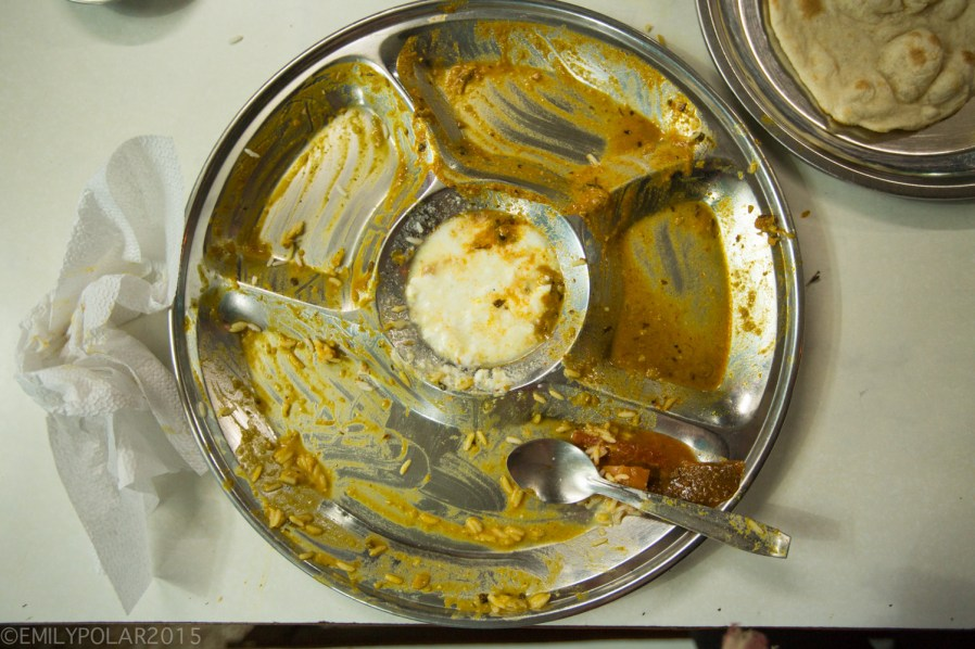 Overhead view of a typical Indian steel plate with only the sauce from Veg Thali left.
