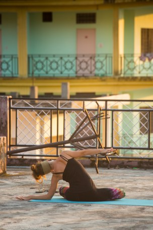 Girl doing yoga on the roof top at sunset in Laxman Jhula of Rishikesh, India.