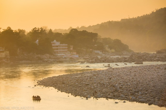 Red rafts float down the Ganges past the north side of Ram Jhula bridge in Rishikesh, India.