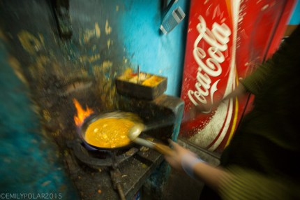 Man stiring a saute pan of Muttar Paneer on a greasy single burner at a restaurant in Rishikesh, India.