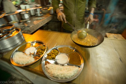 Indian man serving up muttar paneer in hot saute pan to a Thali set steel pan in Rishikesh, India.