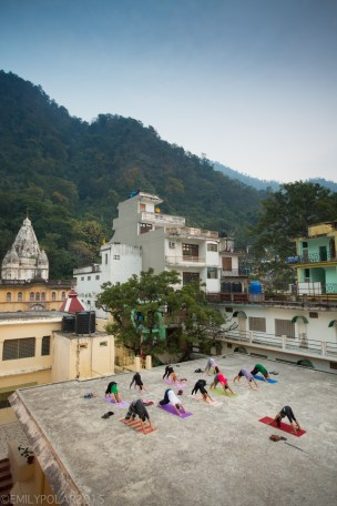 Woman teaching yoga asana on the roof top at sunset in Laxman Jhula, Rishikesh.
