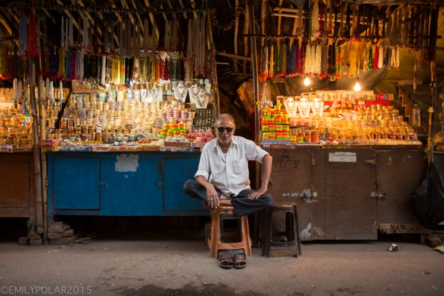 Cool Indian man wearing sunglasses at street stand selling trinkets to tourists in Laxman Jhula, Rishikesh.