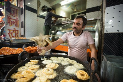 Indian man frying batter in huge vat of oil making sweet jalebi in Rishikesh, India.
