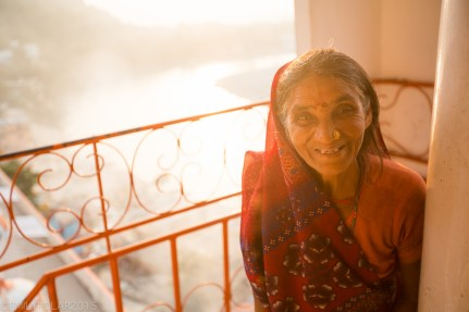 Elder Indian woman with nose ring smiling at the camera in the warm glow of sunset after prayer in Trayambakeshwar Temple, Rishiskesh.