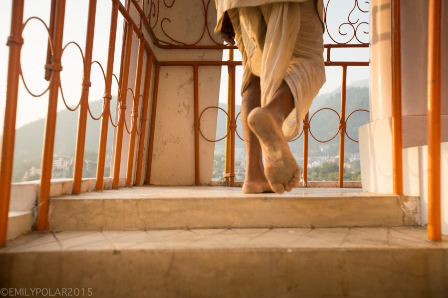 Hindu man walking up the stairs of the Trayambakeshwar Temple in Rishikesh, India.