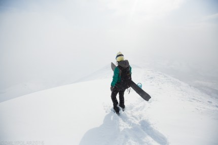 Woman standing on snowy ridge with snowboard in a sunny whiteout at Hirafu, Japan.
