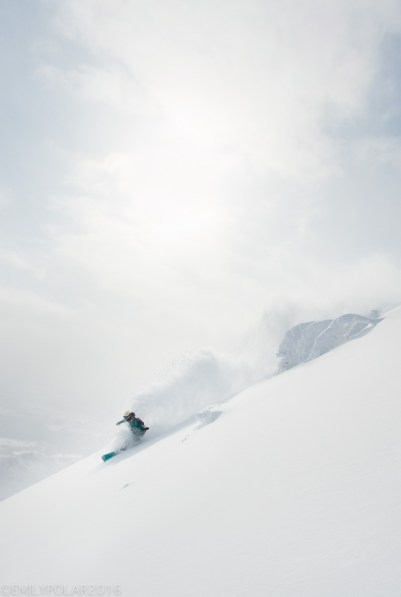 Japanese woman snowboarder slashing some fresh powder at Hirafu Resort in Niseko, Japan.