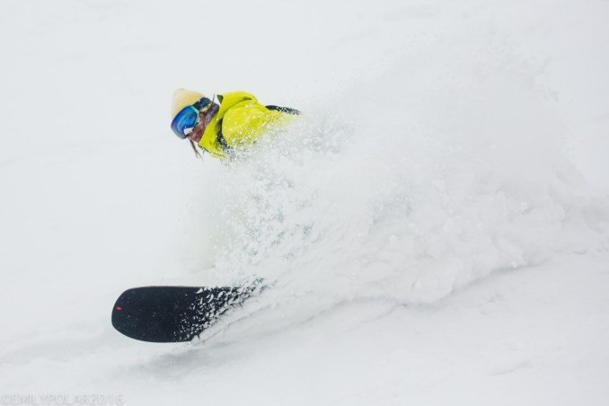 Japanese woman snowboarder riding some fresh powder at Moiwa Resort in Niseko, Japan.