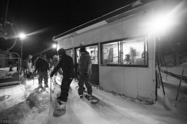 Snowboarders getting on the chair lift at night at Hirafu Resort in Niseko, Japan.