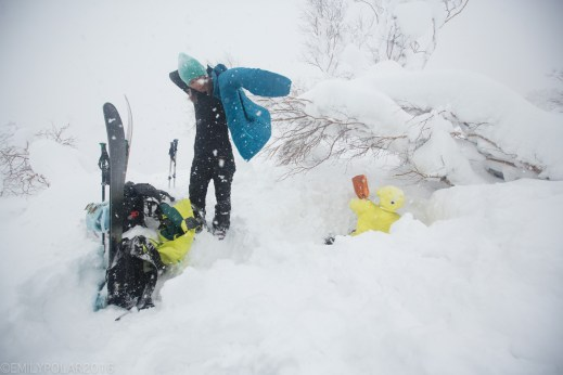 Man and woman snowboarder digging a snow cave on a stormy snow day in the Niimi backcountry in Hokkaido, Japan.