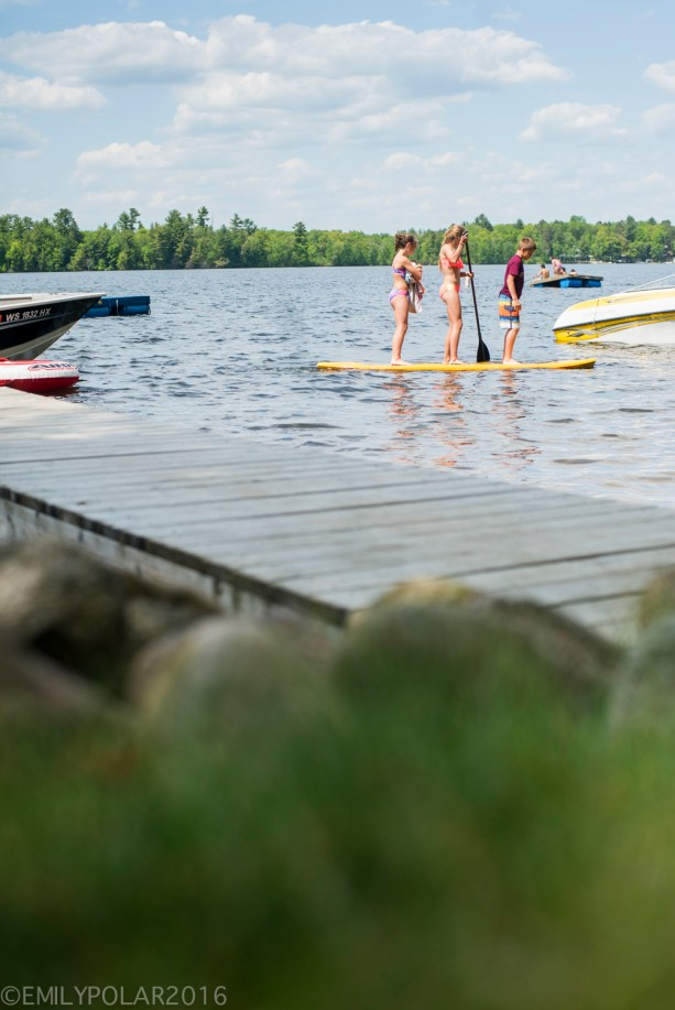Three kids on a stand up paddle Board on Moshawquit Lake in Wisconsin.