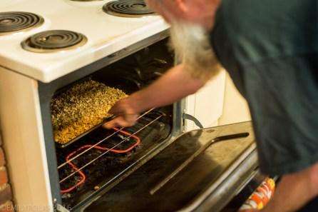 Man making granola pulling the oats out of the oven on a baking pan in his kitchen.