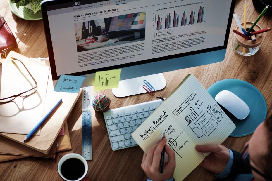 homem faz plano de negócios com um caderno e graficos de crescimento que indicam alta performance