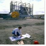 Homme lisant un plan devant une usine en construction - Emplois Industrie