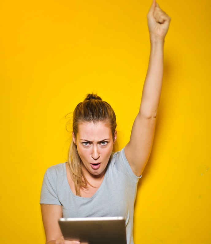 Woman fist pumping in triumph, holding ipad.