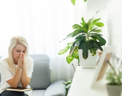 woman sitting on couch praying