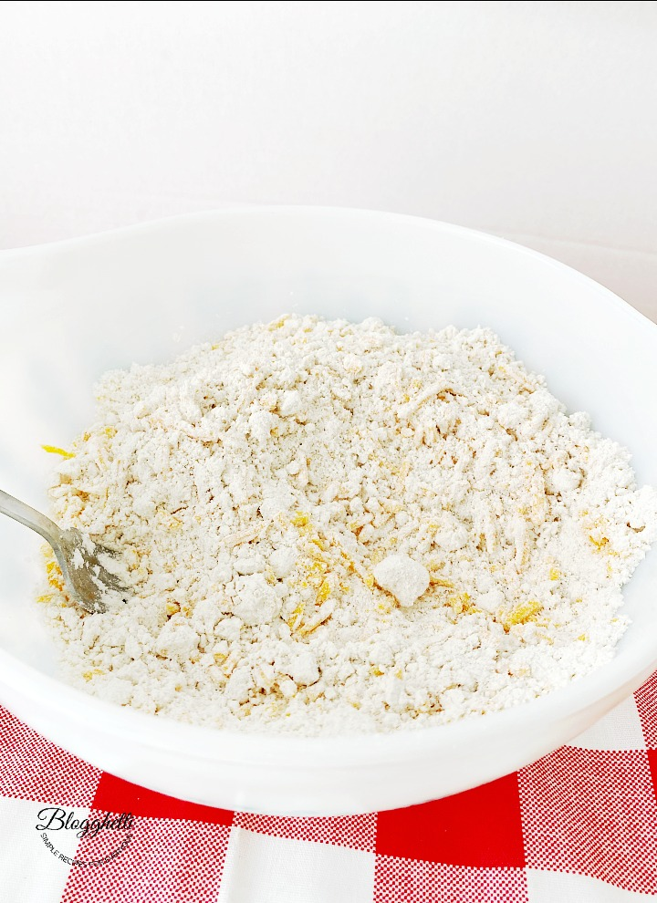 white bowl with flour mixture and cheese for biscuits