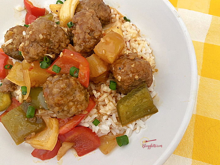 close up of sweet and sour meatballs over rice in white bowl