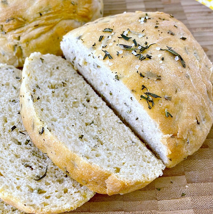 Rosemary bread sliced on wooden cutting board