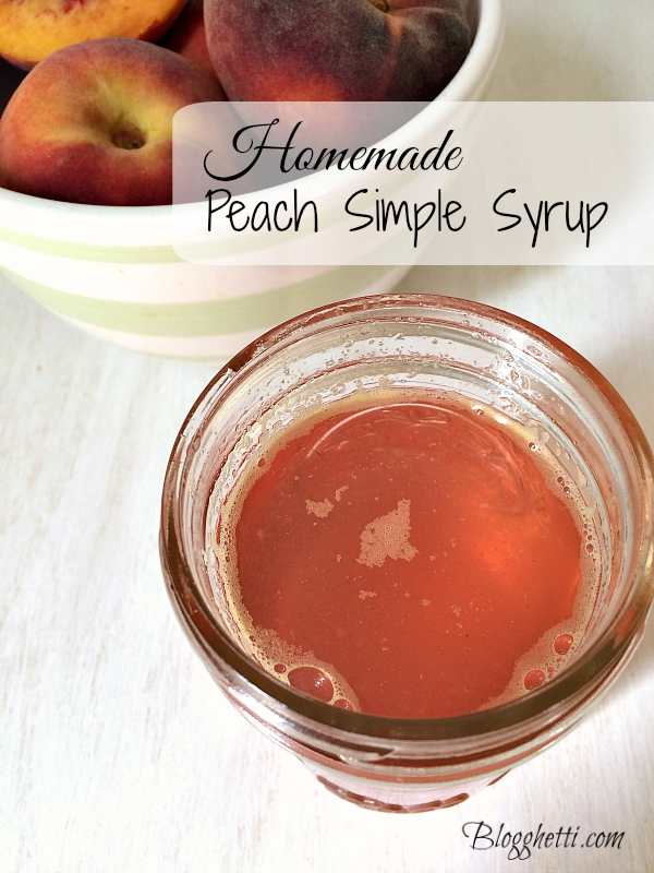 Peach Simple Syrup in mason jar with a bowl of fresh peaches in the background