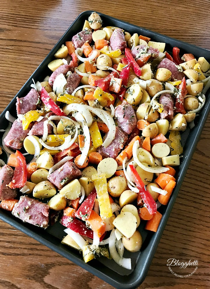 sheet pan with sausage and vegetables ready to roast