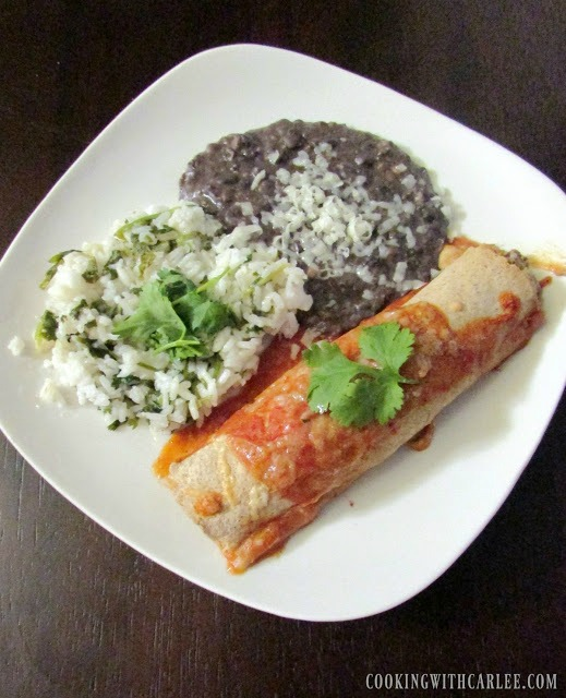 Chicken enchiladas on a white plate with rice and beans