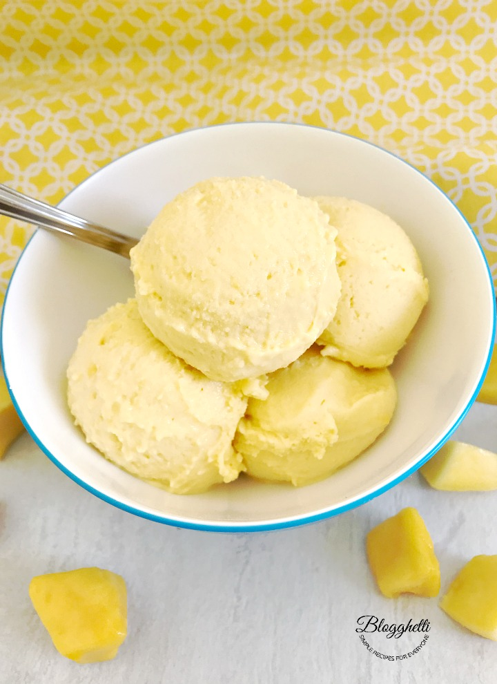 2-Ingredient Mango Sherbet in white and blue bowl with a spoon