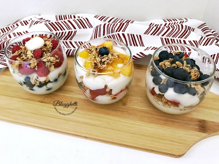 Fresh Fruit and Yogurt in glass containers on a wooden board
