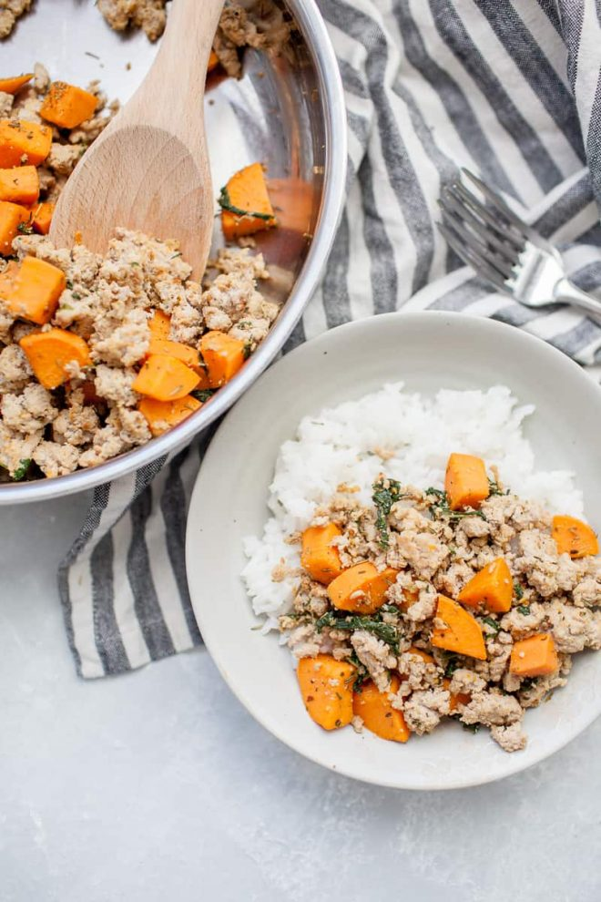 ground turkey with sweet potatoes on white plate with skillet in background