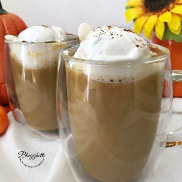 two glasses of pumpkin spice hot chocolate with whipped cream on top